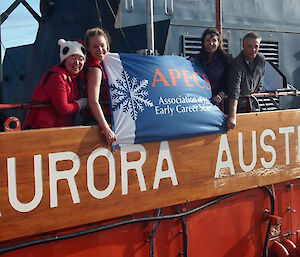 Four young scientists are holding up a flag with saying Association of early career scientists above the rail and the sign of the Aurora Australis