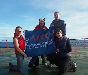 The four young scientists hold up their flag looking very excited about their trip to Antarctica.