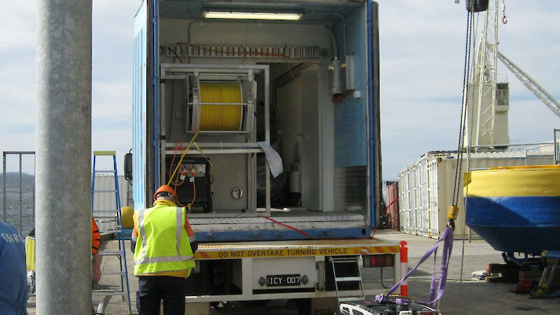 The Remotely Operated Vehicle attached to a crane in front of a shipping container.