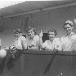 Four female researchers waving from deck of ship.
