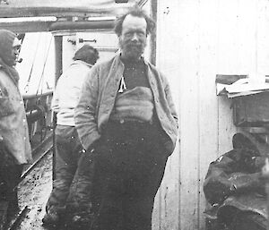 A black and white photograph of a man standing onboard a boat.