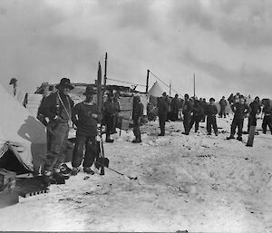A black and white photograph of people and tents on the sea ice.