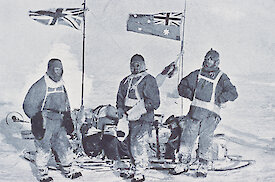 Black and white photo of three men in old-fashioned polar clothes by a sledge.