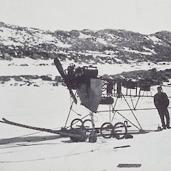 Man standing next to small long tractor adapted from monoplane engine and parts