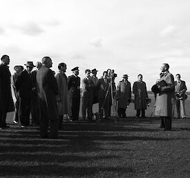 Vintage photo of a varied group of men, some in trench coats with large cameras, listen to a single male speaker