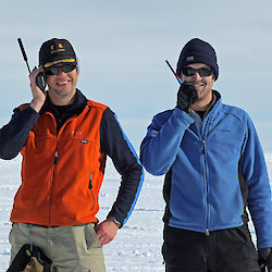 Two expeditioners talk into hand-held radios.