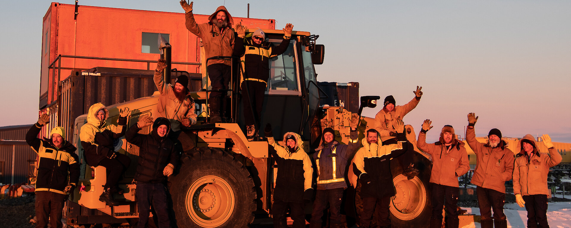 Group of expeditioners standing near loader waving at the camera at sunset