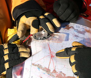Hands on map with a compass