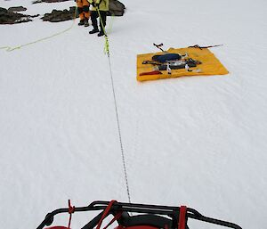 Expeditioners pull rope tied to quad bike