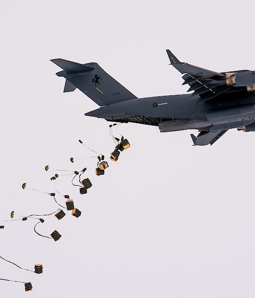 Pallets of supplies attached to parachutes drop from the tail end of a C-17A aircraft.