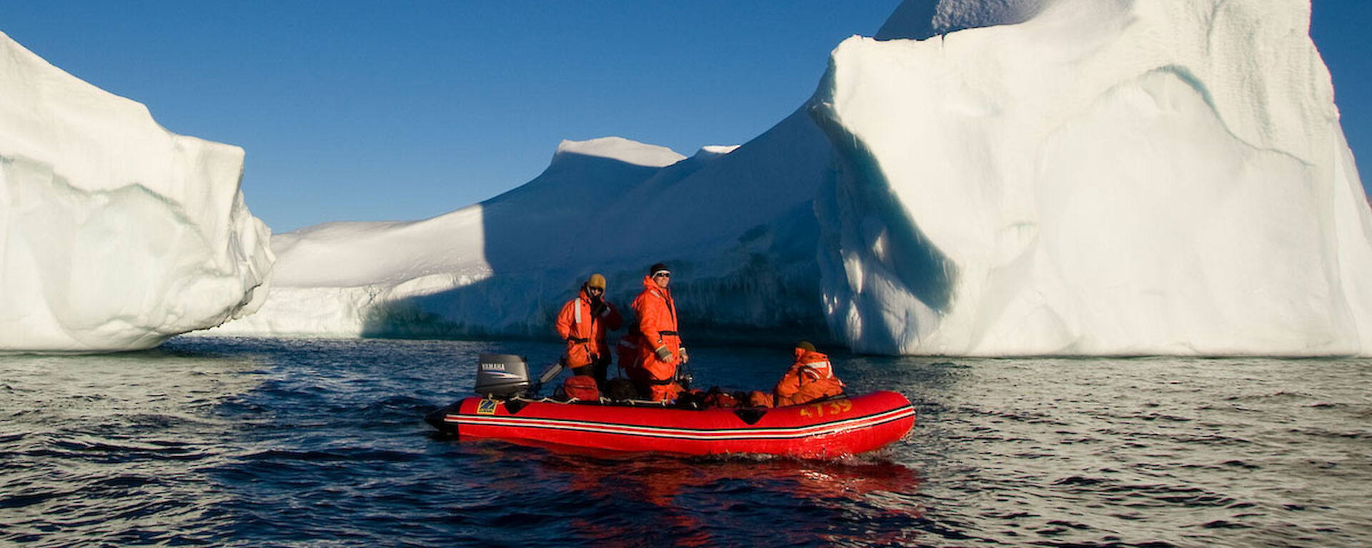 Two people in a red inflatable boat are dwarfed by a huge red iceberg.