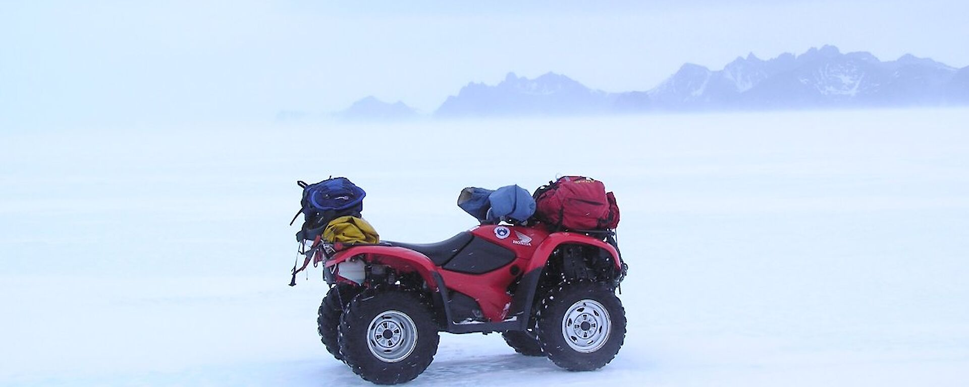 A riderless quad bike stands in some rather icy conditions