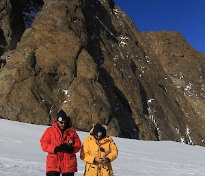 Two expeditioners stand in front of a small peak and use handheld GPS
