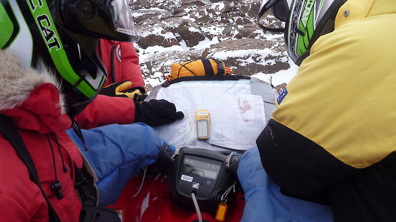 A GPS unit and map lie in the middle of a quad bike, while two expeditioners use them for navigation at a stop.