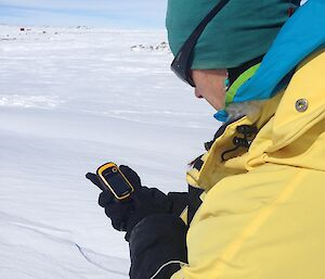 Expeditioner uses GPS in the field with snow all around