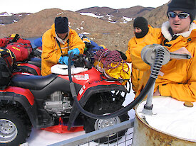 Three men in yellow gear hold pumps to refuel a quad bike