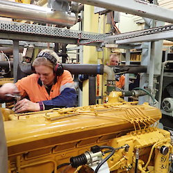 A female mechanic works on a large generator inside the power house at Davis station