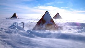 Snow blows around a tent.