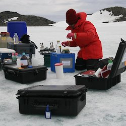Expeditioner kneeling on ice in front of boxes of scientific equipment
