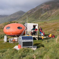 Red round hut set on the grassy slope of the island with expeditioners standing outside.