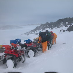 Expeditioners standing near line of quads during blizzard