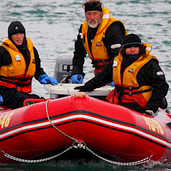 Three people in a zodiac inflatable boat.
