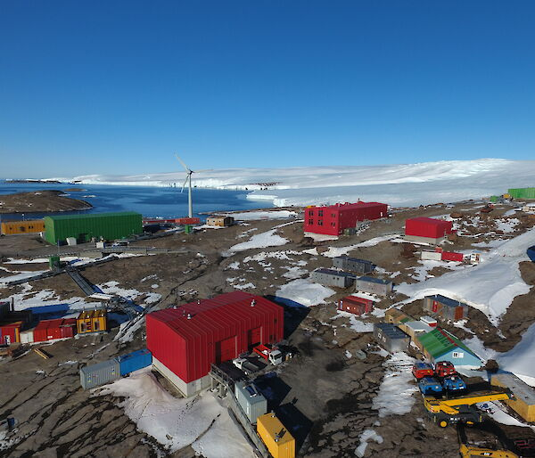 Low aerial view over Mawson station buildings.