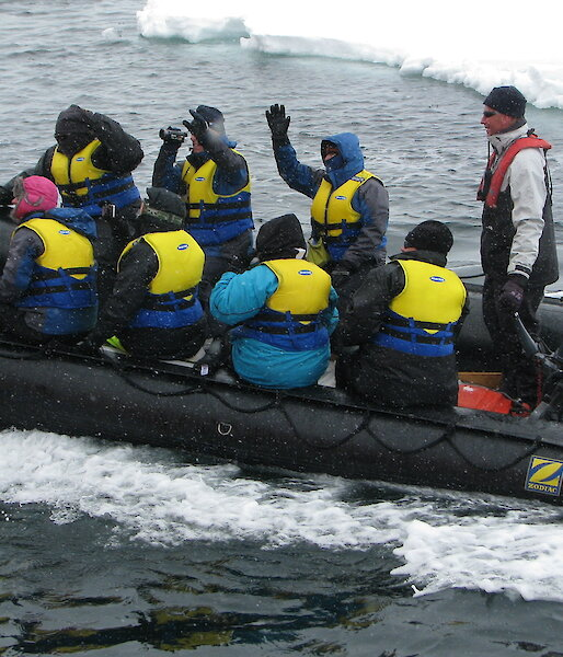 Eight tourists in an inflatable rubber boat, with an ice floe in the background