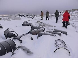 Fuel drums mostly covered with snow. People in the background.