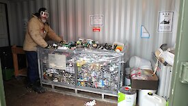 An expeditioner stands next to a cage of bottles and cans.