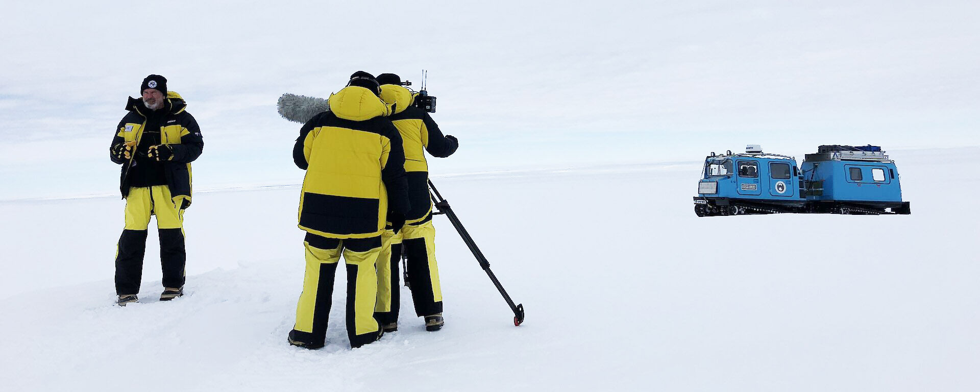 Yellow survival suited film crew on the ice with blue Hagglunds in near distance