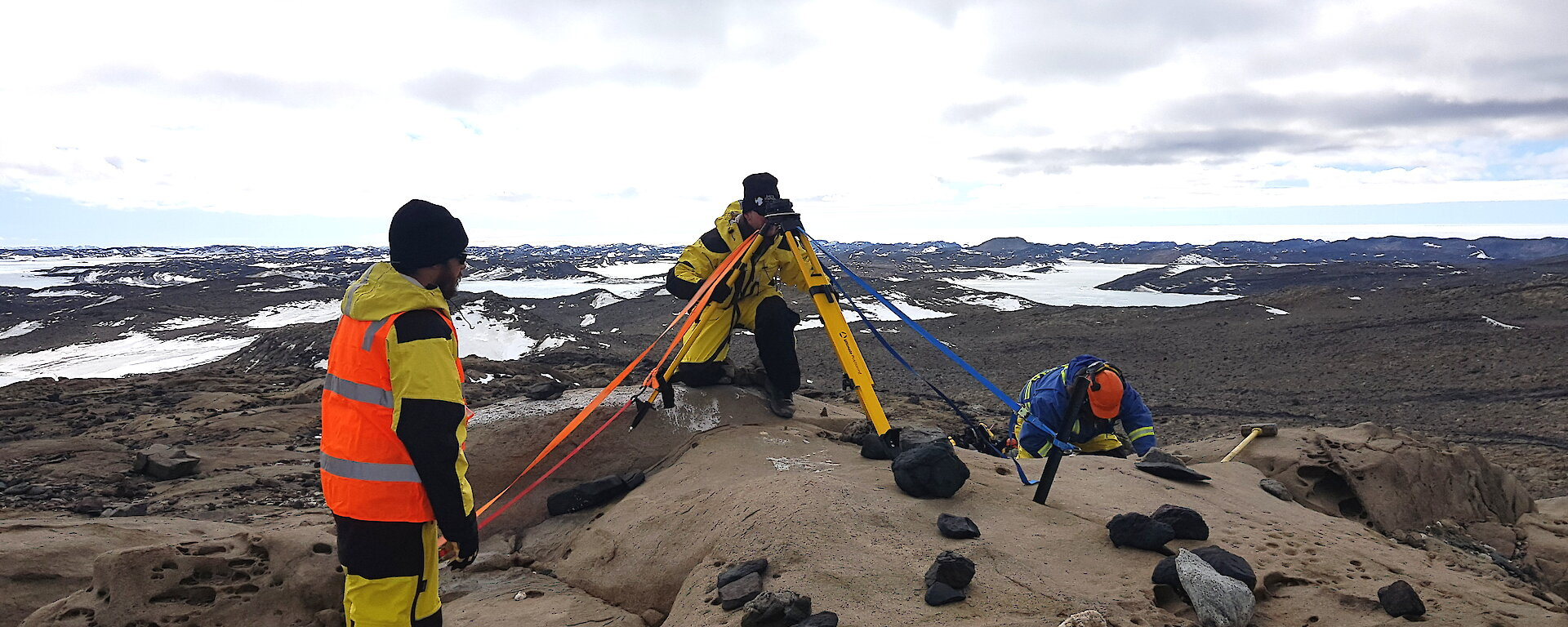 3 people with surveying equipment in a rocky landscape.