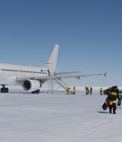 A photo of people walking off a icy runway with a plane in the background
