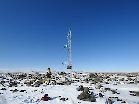 Photo of steel tower in ice and rock landscape