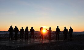 Expeditioners silhouetted against sunset