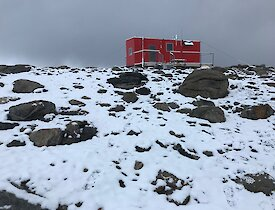 Robbo's hut on a snow and rock covered hill with storm clouds in the background
