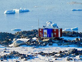 Jack's Donga which is red and blue sitting on rocks overlooking icebergs and the water