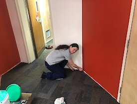 Passing expeditioner symbolically places the final piece of grey carpet tile against a wall for the upper renovations