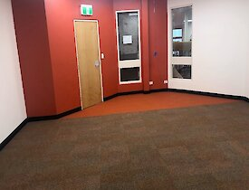 Inside the Red Shed in the library with red and off white walss with new rust, orange carpet