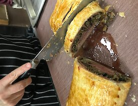 Cutting a pastry to serve the Beef Wellington on a cutting board