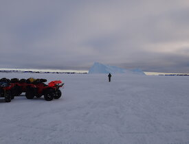 Thre quads stopped on the ice and one person standing in front a gigantic iceberg under a cloudy sky