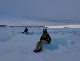 Two expeditioners in full winter dress and quad helmets sitting on large pieces of blue ice
