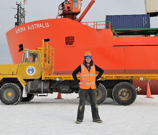 A man is standing on the sea ice in front of a yellow truck parked in front of a red icebreaker ship