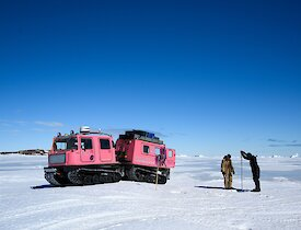 Dan and Mike drilling a fast ice way-point in front of their pink Hägglunds vehicle