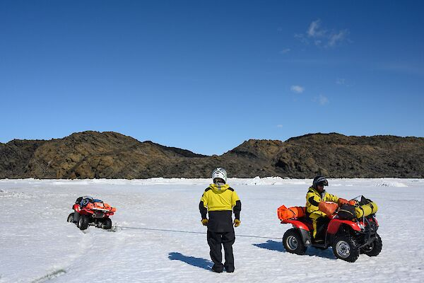 A man stands beside another man on a quad bike as it is being pulled out of the ice