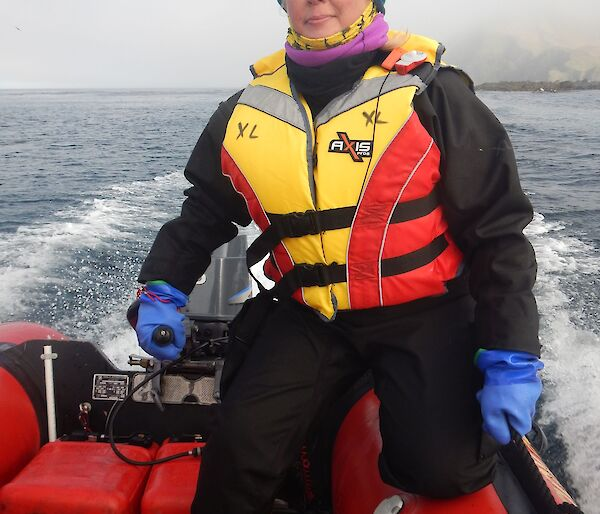 a woman in a life jacket sits at the tiller of a red inflatable boat