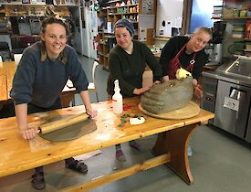Three women are standing around a cake rolling and shaping dough into an elephant seal head
