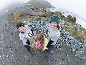 Two women hold an elephant seal cake outside with the station and an elephant seal in the background