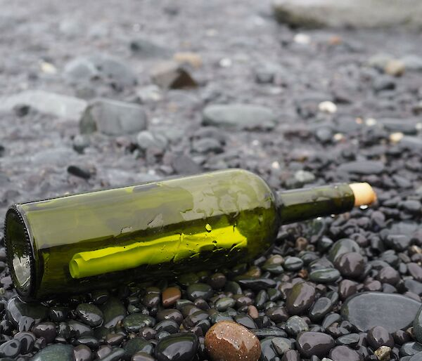 A green bottle lays on a black pebble beach