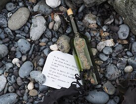 A green bottle lays on a pebbel beach with a typed note next to it